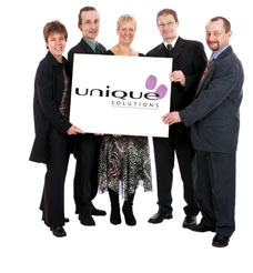 Unique Solutions team of five holding a giant logo poster